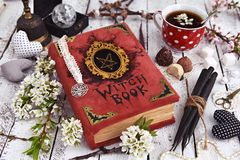 Witch book with black candles, cup of tea and mystic decorations. Occult, esoteric and divination still life. Halloween background with vintage objects royalty free stock photography