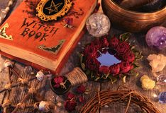 Witch book with magic rose mirror, pentagram and mystic objects on planks. Occult, esoteric and divination still life. Halloween background with vintage objects stock photos