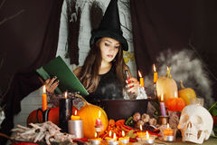 Witch with a book and a test tube of blood Royalty Free Stock Images