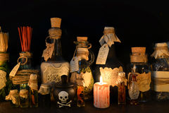 Witch bottles with candle on black. Halloween still life with witch bottles and bloody candle. Halloween image. Signs on labels are not foreign text, these Royalty Free Stock Images