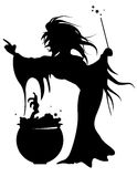 Witch Brewing a Potion in a Cauldron. Silhouette of witch with mixing up a potion in a cauldron Royalty Free Stock Photo