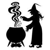 Witch brews a potion in a cauldron Stock Photo