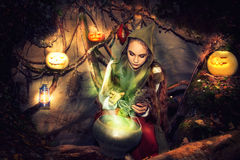 Witch brews potions in her cave. Stock Photo