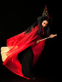 Witch on a broom. Witch with a red cloak, hat and a broom between her legs stock images