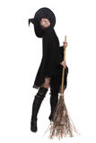 Witch with a broom. Pretty witch dressed in black, posing with a broom Royalty Free Stock Image