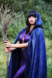 Witch with broom. Beautiful witch with a broom in the forest stock photos