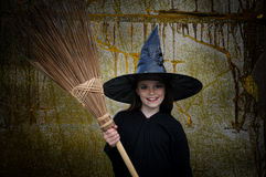 Witch with broom. Portrait of a lLittle witch with broom stock photo