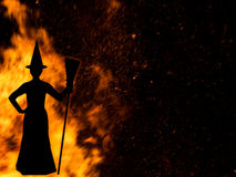 Witch with broomstick silhouetted against fire, Halloween. Stock Images