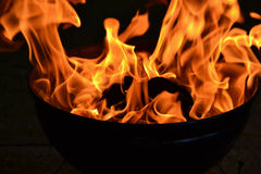 Witch Caldera. Barbecue flame in black caldera against black background stock images