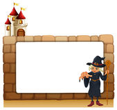 A witch with a cane in front of the empty signboard Royalty Free Stock Photography