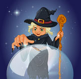 A witch with a cane in front of a magical ball Royalty Free Stock Photo