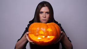 Witch with a carved pumpkin. Halloween concept stock footage