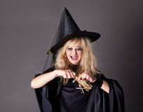 Witch casts a spell on a doll Stock Photos
