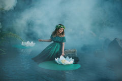 Witch casts a spell on the water in the fog Royalty Free Stock Photo