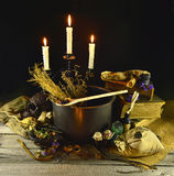 Witch cauldron. Halloween still life of witch cauldron, old books, burning candles, skull and magic objects on wooden table Stock Images