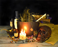 Witch cauldron 2. Halloween still life of witch cauldron, old books, burning candles, skull and magic objects on wooden table Royalty Free Stock Photography