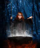 Witch with cauldron at night forest Stock Photography