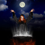 Witch with cauldron on night sky background Royalty Free Stock Image