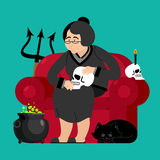 Witch in chair. Skull and black cat. Sorceress and Magic Pot Pot Royalty Free Stock Image