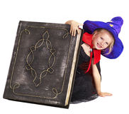 Witch child holding  book. Royalty Free Stock Photo