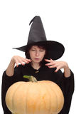 Witch conjuring. Pretty witch in black hat, raising her hands and conjuring over a large pumpkin Royalty Free Stock Photography