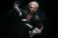 Witch conjuring. Blond hair witch, conjuring with old book Royalty Free Stock Photos