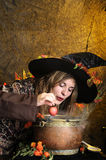 Witch cooking in a copper cauldron Royalty Free Stock Images