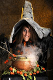Witch cooking in a copper cauldron Stock Photo