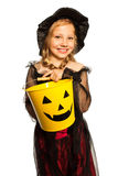 In witch costume holding Halloween bucket Stock Images