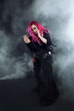 Witch creates magic. Attractive woman with red hair in witches costume Royalty Free Stock Photos