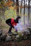 Witch with creepy smoking pumpkin in forest. A red haired witch casting a spell leaning over a gnarly, creepy pumpkin on a stone wall with purple smoke royalty free stock image