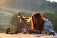 Witch with crystal ball at sunset stock images