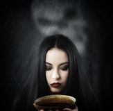 Witch with a cup of potion Stock Images