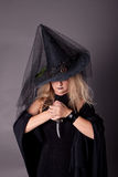 Witch with a dagger in his hands. In black clothes and hat Royalty Free Stock Photo