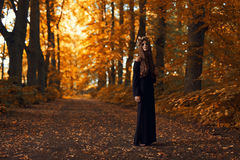 Witch in dark forest. The young beautiful witch in dark forest Royalty Free Stock Photo