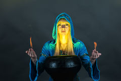 Witch with fire in hands. Creates a spell royalty free stock photography