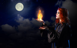 Witch with flame on night sky background stock images