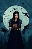 Witch in full moon. A young witch in a black dress on background of a full moon and a flock of crows. Fantasy illustration. Fairy tale Royalty Free Stock Photo