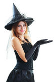 Witch halloween. Beautiful young girl in witch halloween costume and in black gloves hold empty palms. Halloween party advertizing concept Royalty Free Stock Image