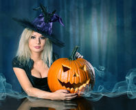 Witch with Halloween pumpkin. Beautiful girl Stock Photos