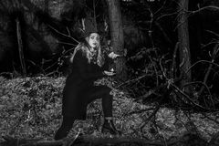 Witch with a hand-held lantern in the. Forest. Witchcraft Halloween Royalty Free Stock Images
