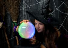Witch in a hat with a ball of fate. In his hands Royalty Free Stock Photography