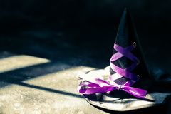 Witch hat on dark table. Halloween holiday concept. Witch hat on dark concrete. Halloween holiday concept. light fleak from window royalty free stock photo