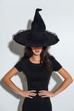 Witch in hat. Halloween. Charming brunette witch in black dress and a hat. Halloween Beautiful young woman in witches hat royalty free stock image