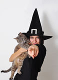 A witch and her cat. A teenager witch and her cat, pointing finger stock image