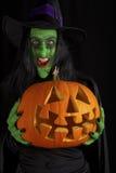 Witch and her pumpkin. Witch and her pumpkin, black background stock image