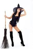 Witch, holding a broom, looks into. Very sexy young brunette is a witch, holding a broom, looks into Stock Photography