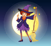 A witch holding a broom standing at the center of a moon Stock Images