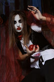 Witch holding a heart in her hand. Halloween, mysticism, magic, mystery. Makeup in the style of Billy doll. Witch holding a heart Stock Photo