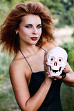 Witch holding a human skull Royalty Free Stock Images